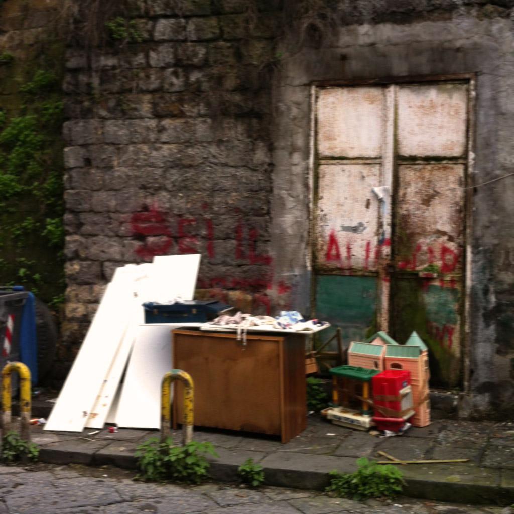 Die Straßen in Neapel sind mit schwarzen Basaltsteinen gepflastert. Das Bild zeigt eine Hauswand aus gelben Tuffsteinen. Vor der Wand ist Sperrmüll abgestellt.