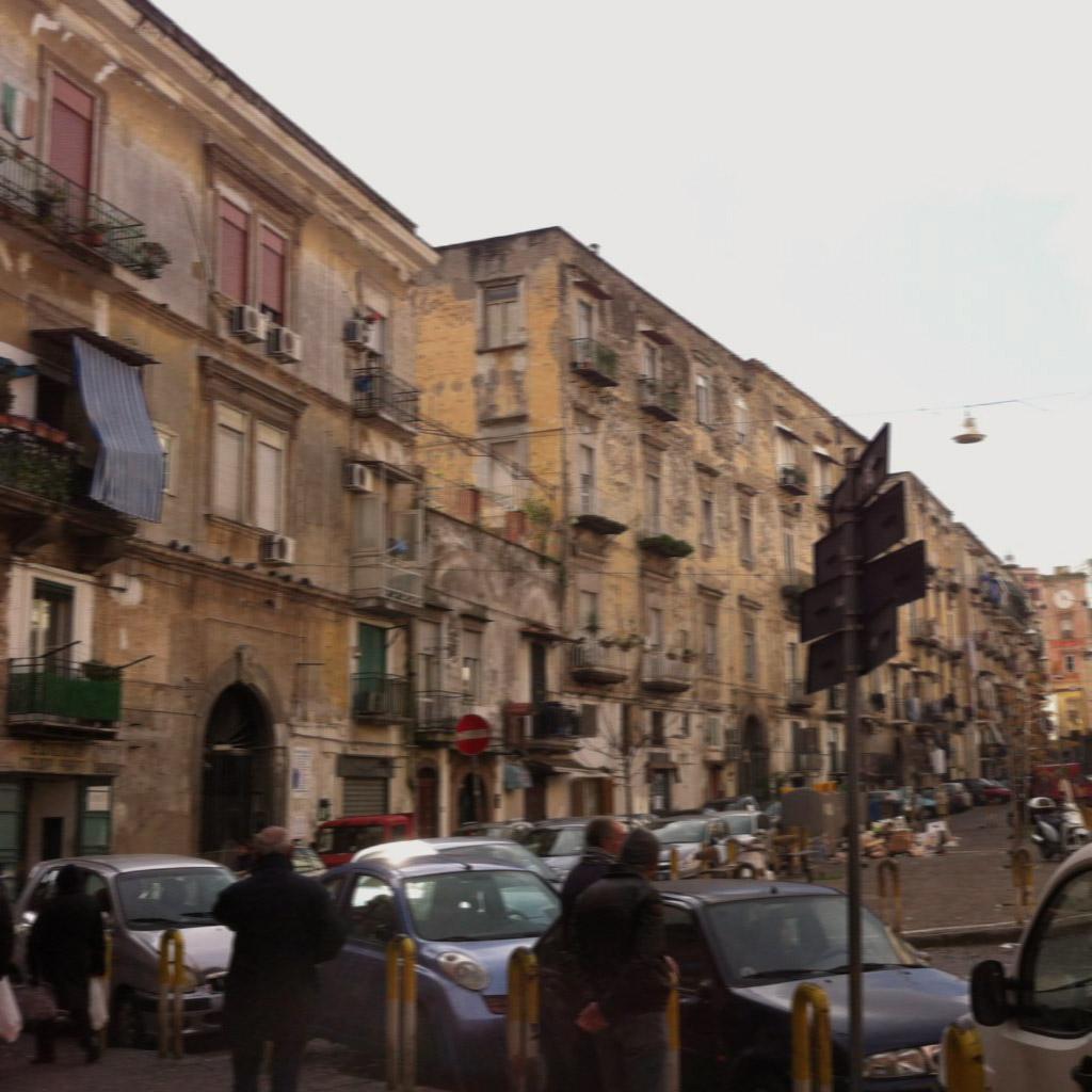 Das Bild zeigt einen Platz in Neapel. Den Hintergrund bilden alte Häuser, von denen der gelbe Putz hinunter blättert. Im Vordergrund sind Kleinwagen geparkt, der Himmel ist grau.