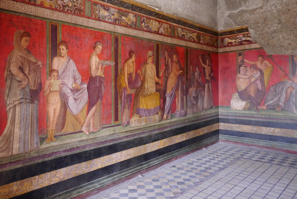 Ein Fresko mit vielen lebensgroßen Gestalten vor rotem Grund aus der Villa dei Misteri in Pompeji.