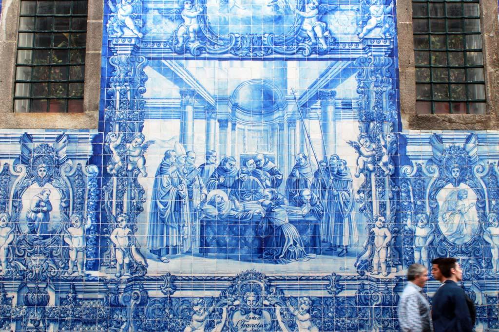 Porto, Kunst des Alltags: Fromme Bilder – hier der Tod des Heiligen Franziskus – sind für Kirchen nichts Ungewöhnliches. Das Material schon. Südliche Außenwand der Capela das Almas an der U-Bahn-Station Bolhão.