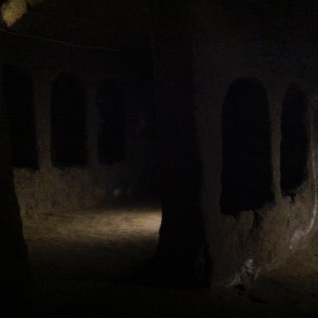 Unterirdischer Raum in den Katakomben von San Gaudeoso. An den Seiten schmale Nischen mit Rundbögen, die aus dem dunklen Tuff herausgeschlagen worden sin, das Licht ist dämmerig..