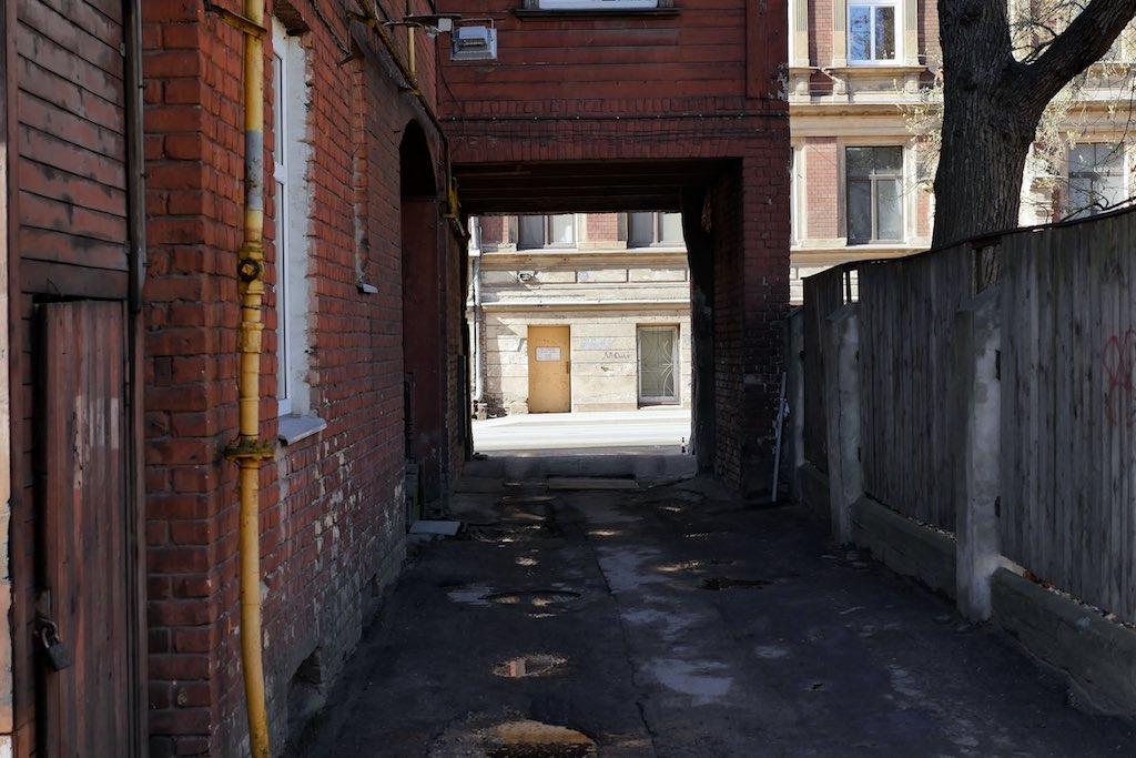 Hofdurchfahrt zu einem Hinterhof mit Holzhäusern in Riga.