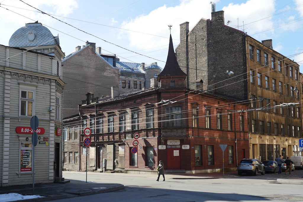 Straßenecke in Riga mit zwei Holzhäusern.