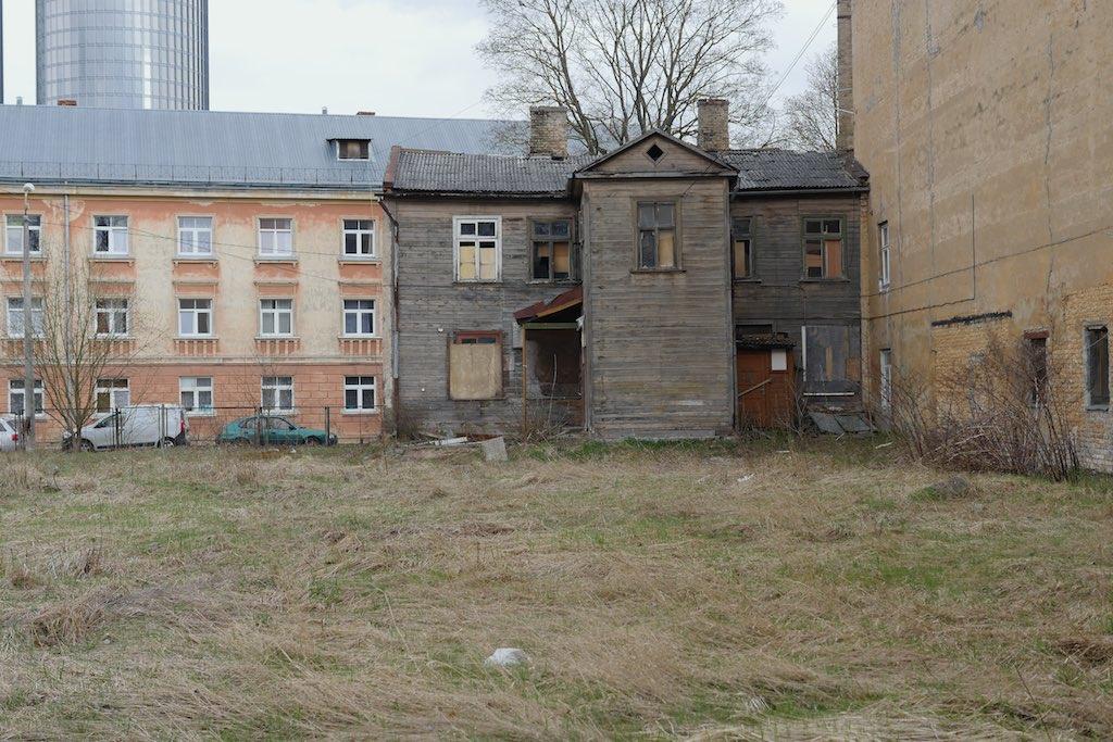 Ein verfallenes Holzhaus in Riga Padaugava auf einer Wiese.