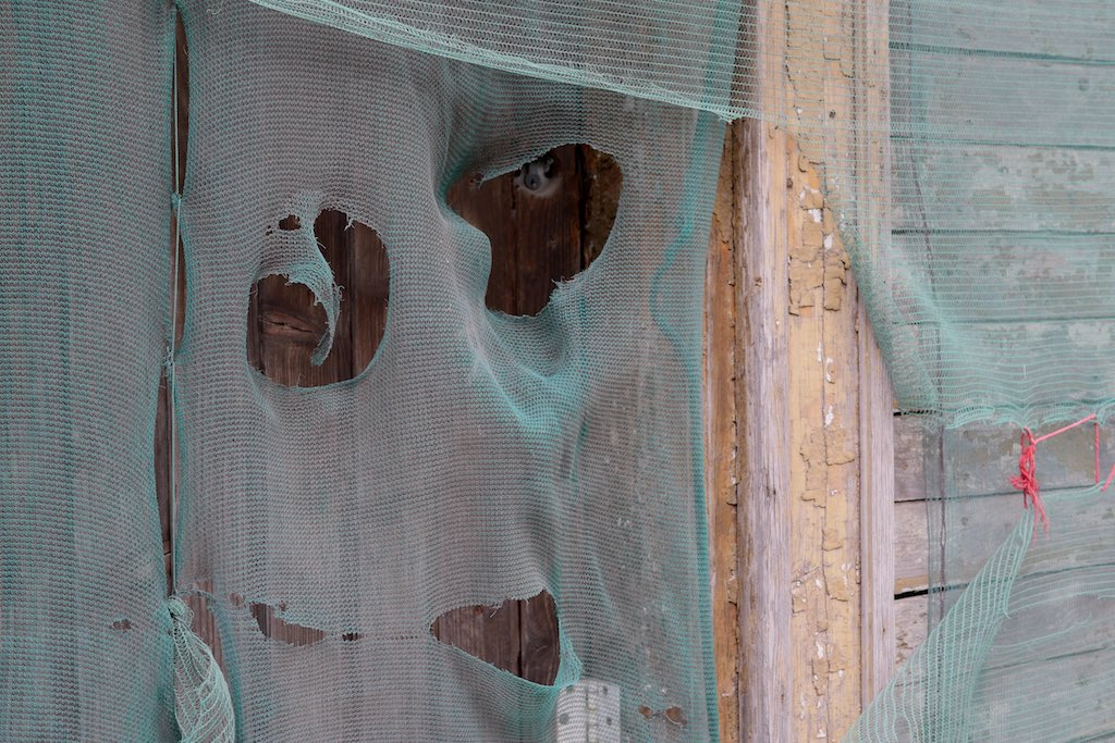 Fassade eines Holzhaus in Riga mit Planen verhängt.