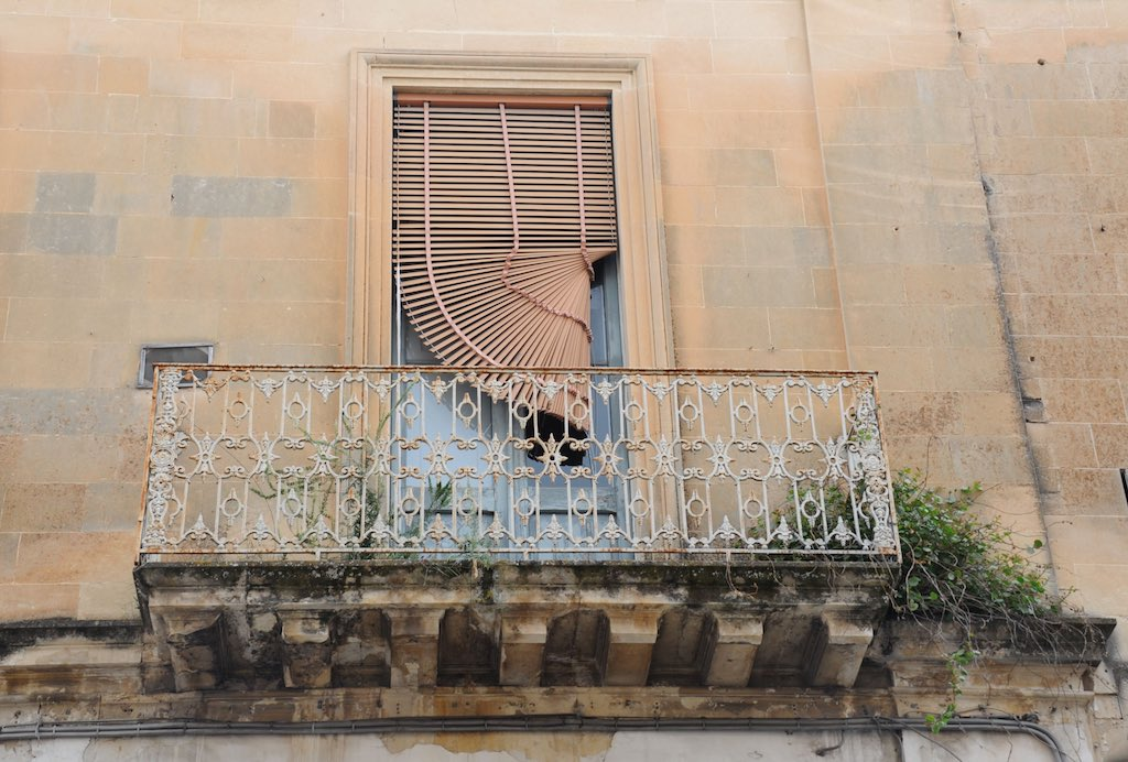 Eine typische Fassade in Lecce, eine gelbe Wand, ein kleiner Balkon und einige Spuren des Verfalls.