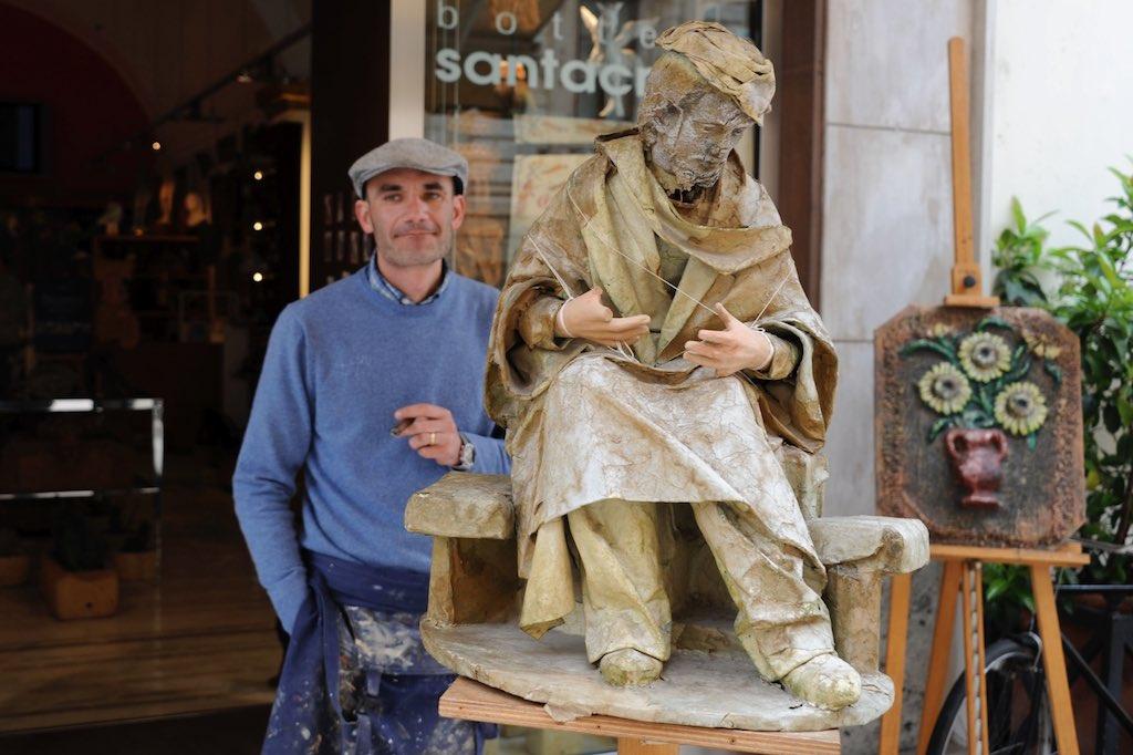 Ein Krippenbauer aus Lecce steht vor seinem Geschäft und raucht.
