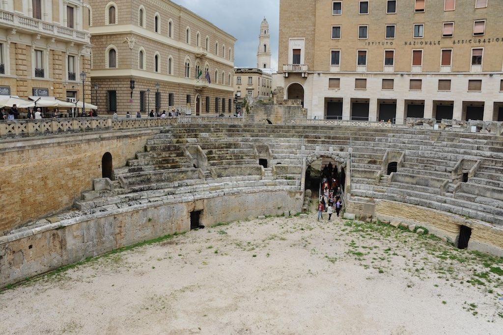 Blick in die Arena des römischen Theaters von Lecce. Die Zuschauerränge sind aus weißem Kalkstein. Im Hintergrund gebäude aus der Zeit des Faschimus