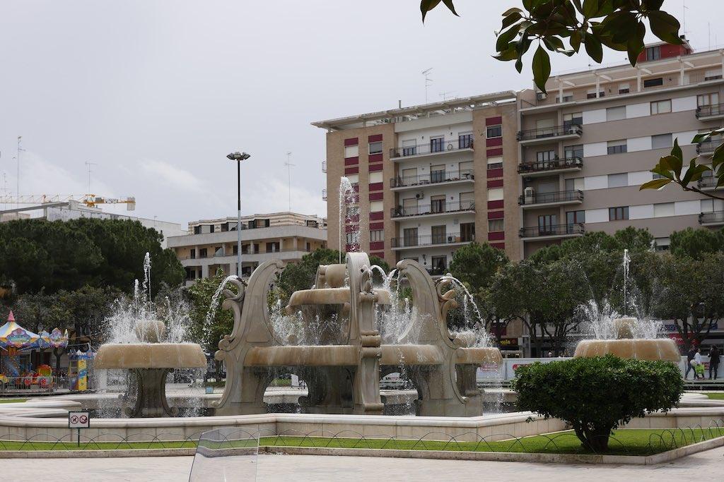 Blick auf einen Brunnen und seine Fontänen in Lecce. Im Hintergrund moderne Hausfassaden aus den 70er Jahren.