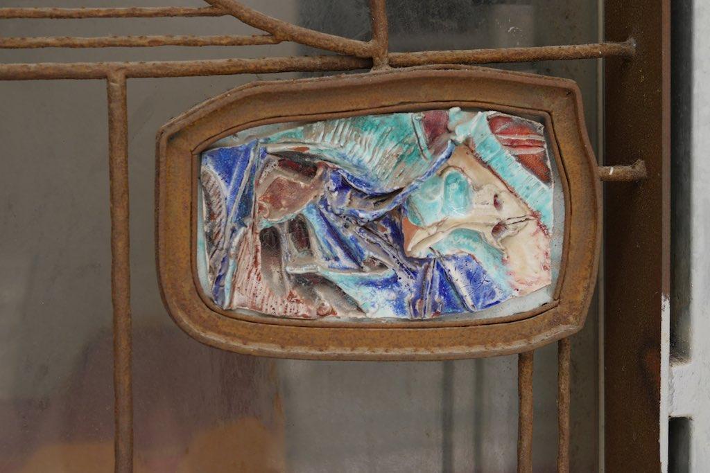 Detail einer Türdekoration aus Metal und Terrakotta.