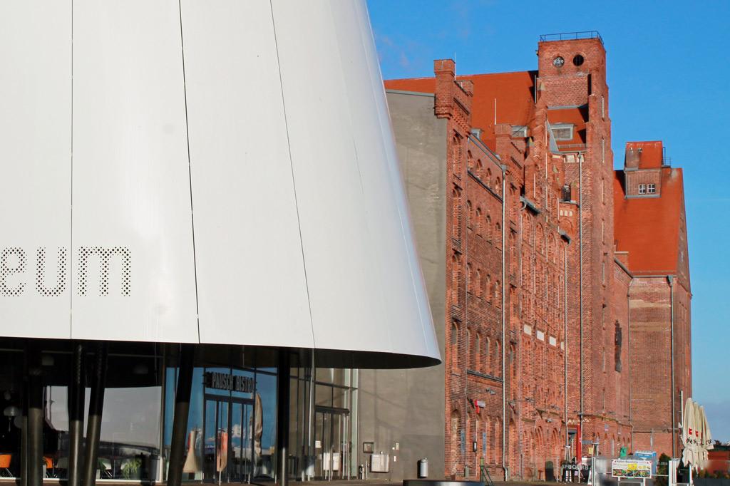 Stralsund: Sagen wir mal so: Die weißen Rundungen passen zur Gorch Fock – sie wirken, als bliese da jemand ein Segel auf. Die backsteinroten Speicherbauten stehen steif und hanseatisch daneben, als wollten sie nichts damit zu tun haben. Und so ist es auch.