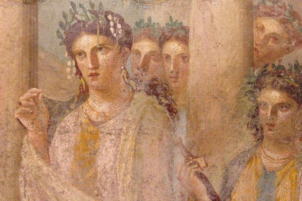 Das Bild zeigt ein Fresko aus den Nationalmuseum in Neapel auf dem junge Frauen aus der römischen Antike mit Kränzen im Haar gezeigt werden.