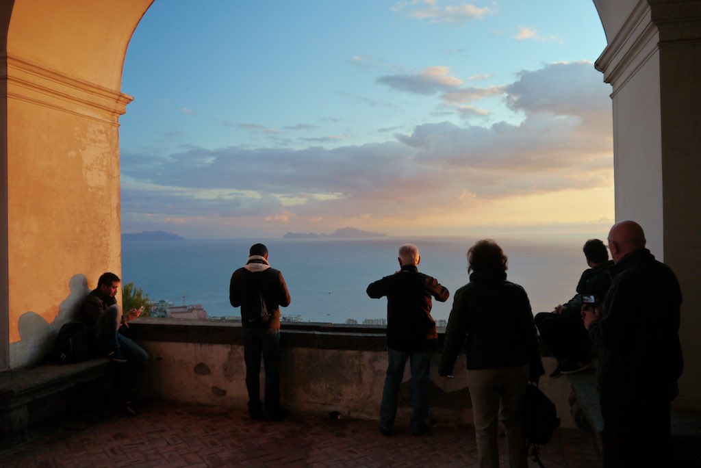 Menschen blicken von einem Balkon auf den Sonnenuntergang über dem Golf von Neapel