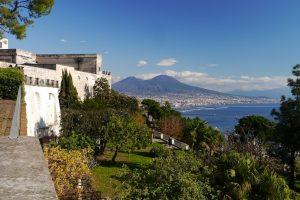 Das Bild zeigt einen Blick übde den Golf von Neapel. Der Himmel ist blau und fast wolkenlos. Im Hintergrund erheben sich die Gipfel des Vesuvs zu dessen Füßen das blaue Meer des Golf von Neapels. Der Blick von den Terrassen der Abtei von San Martino ist ein absoluter Neapel Tipp. Von hier oben ist die ganze Schönheit der Landschaft am Golf von Neapel zu erleben.