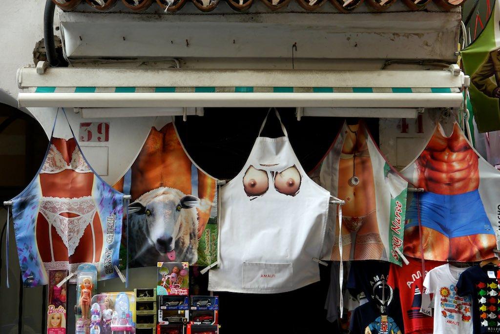 Schürzen mit aufgeruckten Busen und Waschbrettbäuchen in einem Laden in Amalfi