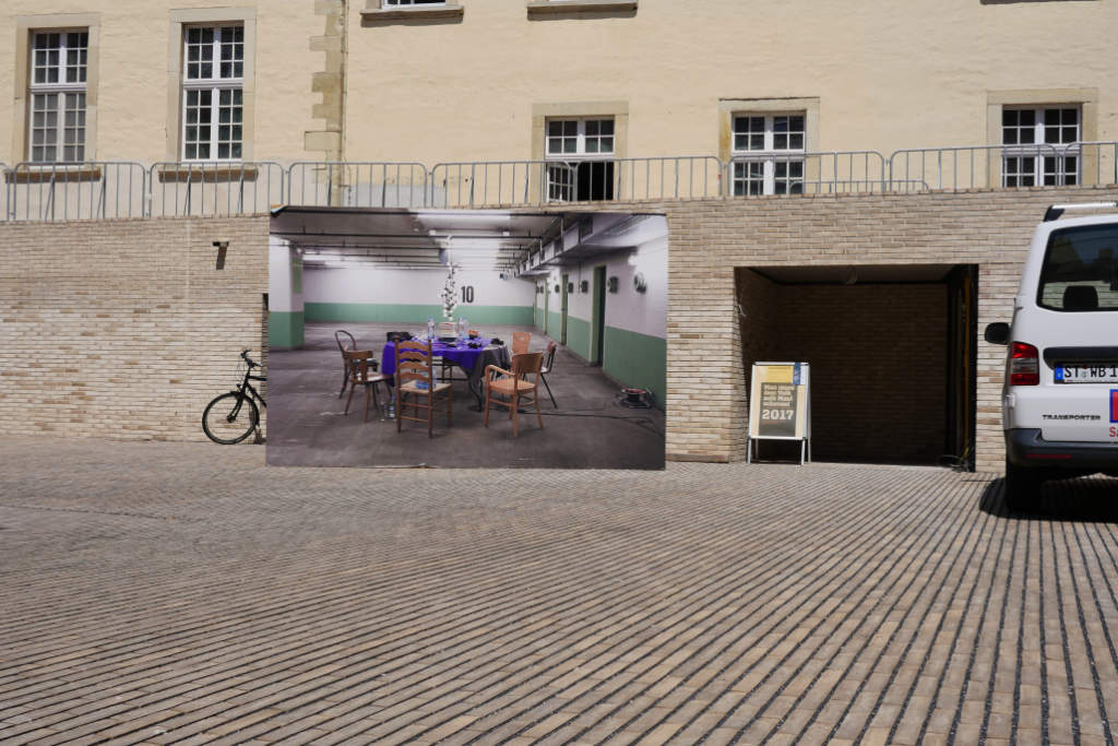 Großformatige Fotografie einer Tiefgarage neben einer Einfahrt.