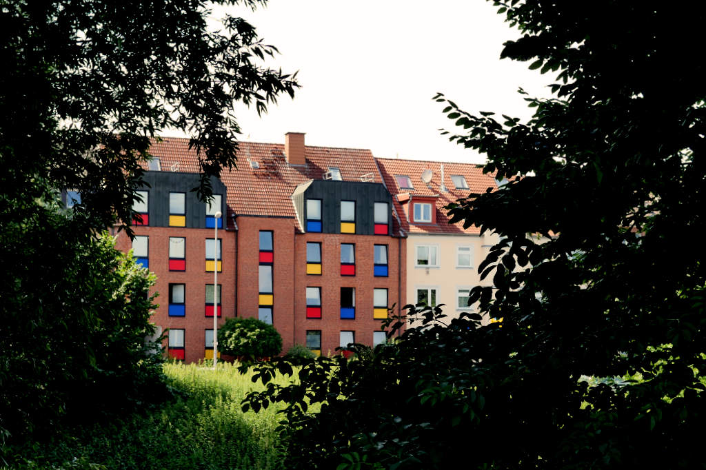 Ein Wohnhaus aus den 70er Jahren mit sehr bunten Fensterrahmen an der Promenade von Münster.