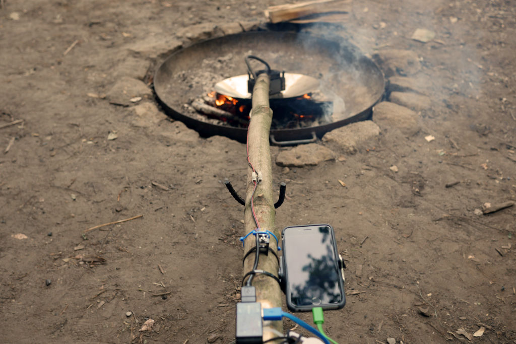 Ein Handy wird mit Der Energie eines Lagerfeuers aufgeladen.