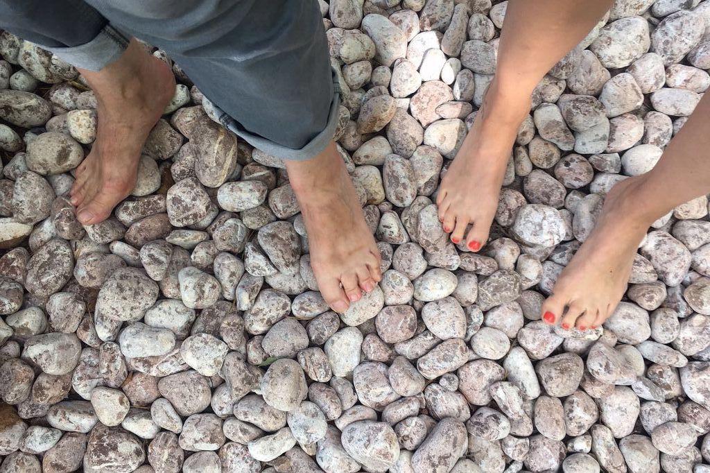 Zwei Paar Frauenfüße stehen barfuß auf runden und ovalen Kieselsteinen. Dies ist eine der über 60 Stationen im Barfußpark Beelitz.