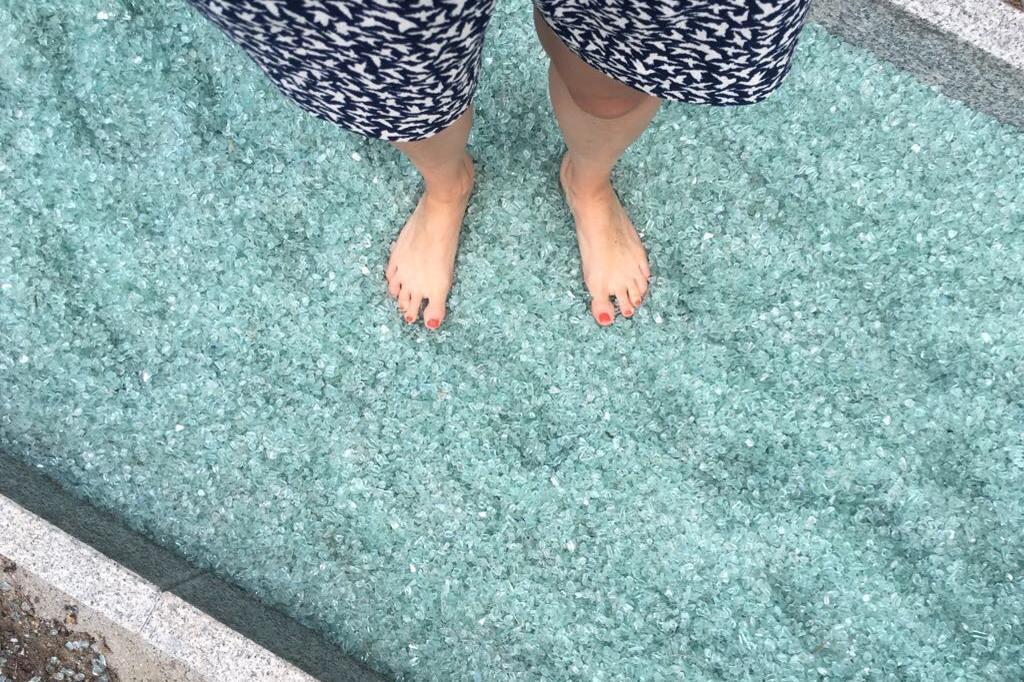 Ein paar nackte Frauenfüße stehen auf blau-türkisem Untergrund. Was aussieht wie Eis, Hageltropfen oder Scherben, ist geschliffenes Glas. Eine weitere Station im Barfußpark Beelitz