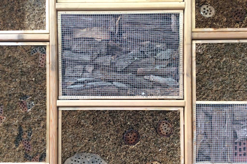 Sieben verschiedene Felder, die durch Holzrahmen voneinander getrennt sind, geben den Blick frei auf durchlöcherte Wandstrukturen und Netze, hinter denen sich Hölzer verbergen. Bei dem Bild handelt es sich um ein Insektenhotel, nicht um ein abstraktes Relief.