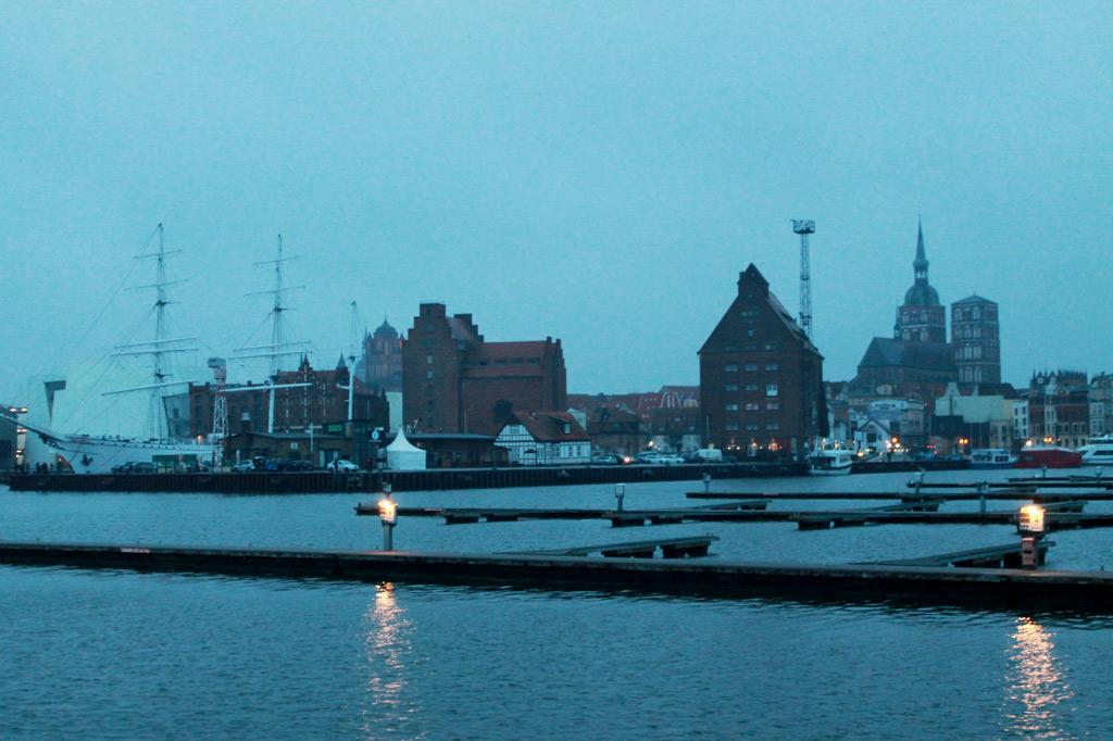 Spielkartenfabrik: Selbst bei Regenwetter imposant: das Hafenpanorama von Stralsund. Links liegt die Gorch Fock, die Türme am rechten Bildrand gehören zur Nikolaikirche.