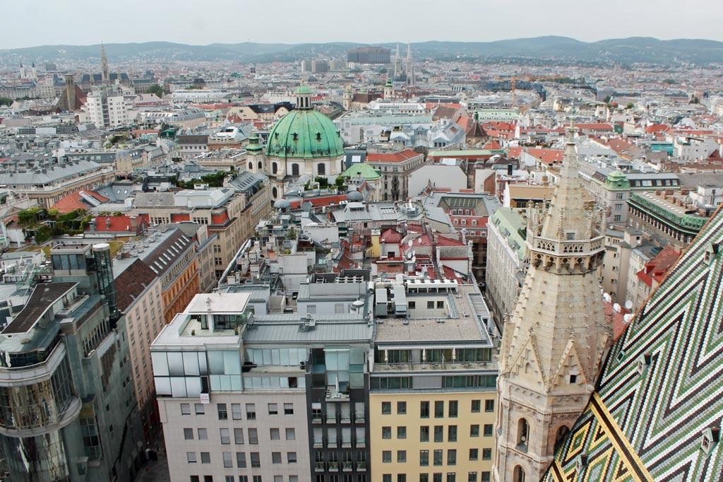 Über den Dächern von Wien. Am linken Bildrand ist der schlanke Turm des gotischen Rathauses zu sehen, hinten mittig ragen die beiden hellen Türme der ebenfalls gotischen Votivkirche in die Höhe.