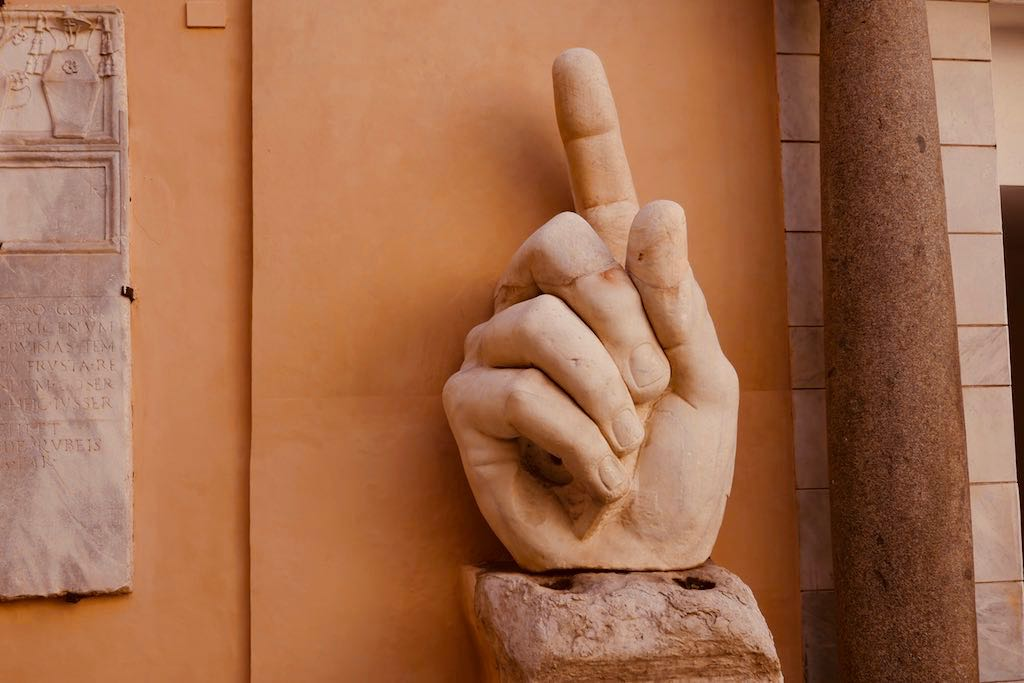Marmorhand mit ausgestrecktem Zeigefinger vor einer okerfarbenen Wand in den Kapitolinischen Museen von Rom. Ein echter Rom Tipp.