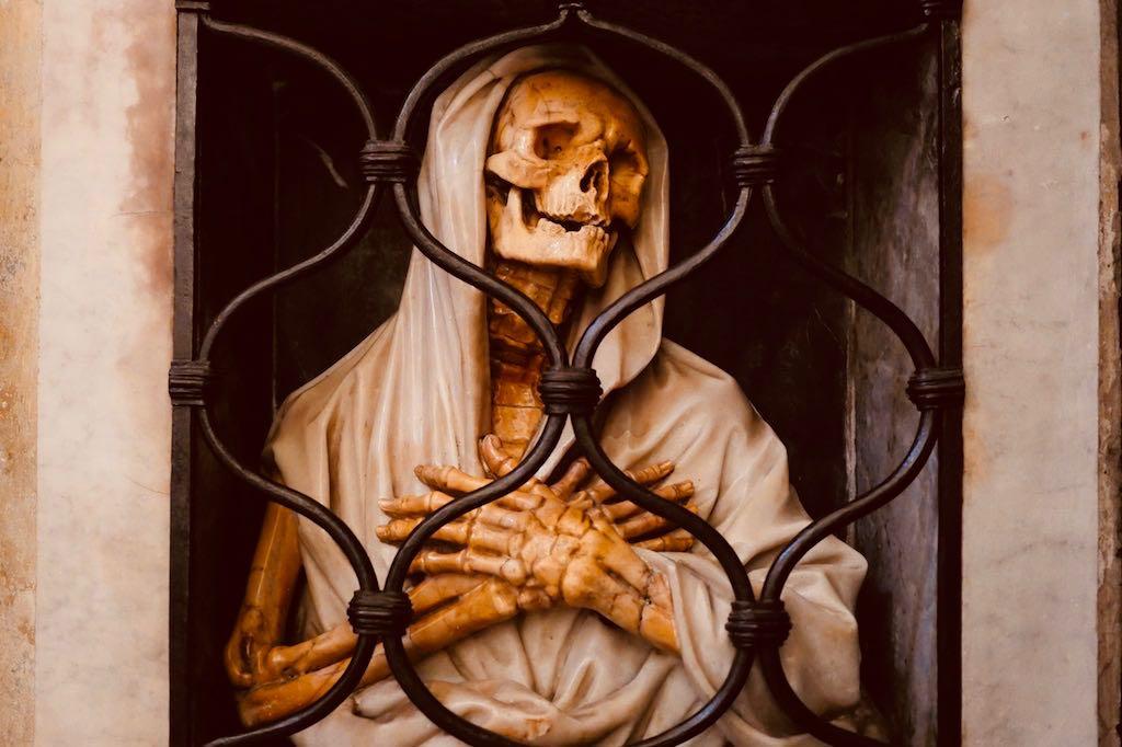 Hinter einem geschwungenen Gitter ein bekleidetes Totengerippe aus gelbem Marmor, gekleidet in einen faltigen weißen Marmormantel. Grabmal im Rom Tipp Santa Maria del Popolo.