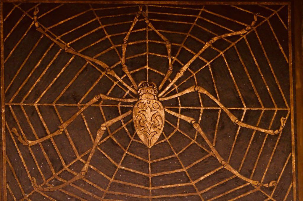 Eine goldene Spinne mitten in ihrem goldenen Netz vor schwarzem Hintergrund.