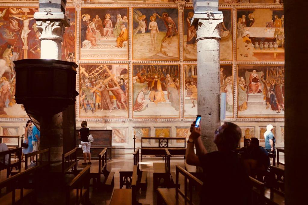 Ein Kircheninnenraum. Besucher fotografieren Bilder aus dem Leben Christi, die in viereckigen Malfeldern auf die Kirchenwand gemalt worden sind
