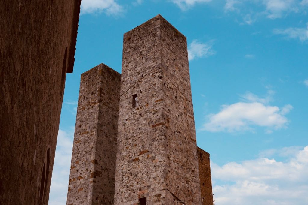 Zwei schmal aufragende Geschlechtertürme in San Gimignano. Die Türme sind aus quadratischem Grundriss errichtet und stehen eng beieinander. Das Material ist weißer Kalkstein.