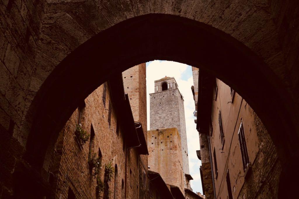 Ein Backsteinbogen in San Gimignano. Duchblick auf einen Geschlechterturm
