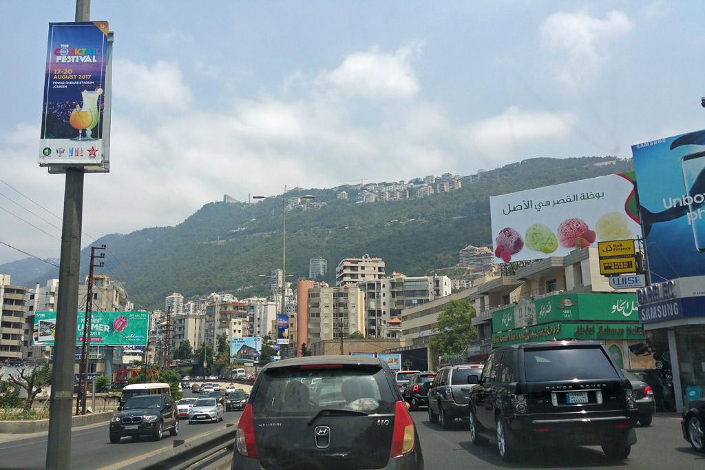 Libanon: Stadtautobahn in Beirut mit Reklameschildern, Hochhäusern und den Ausläufern des Libanon-Gebirges im Hintergrund