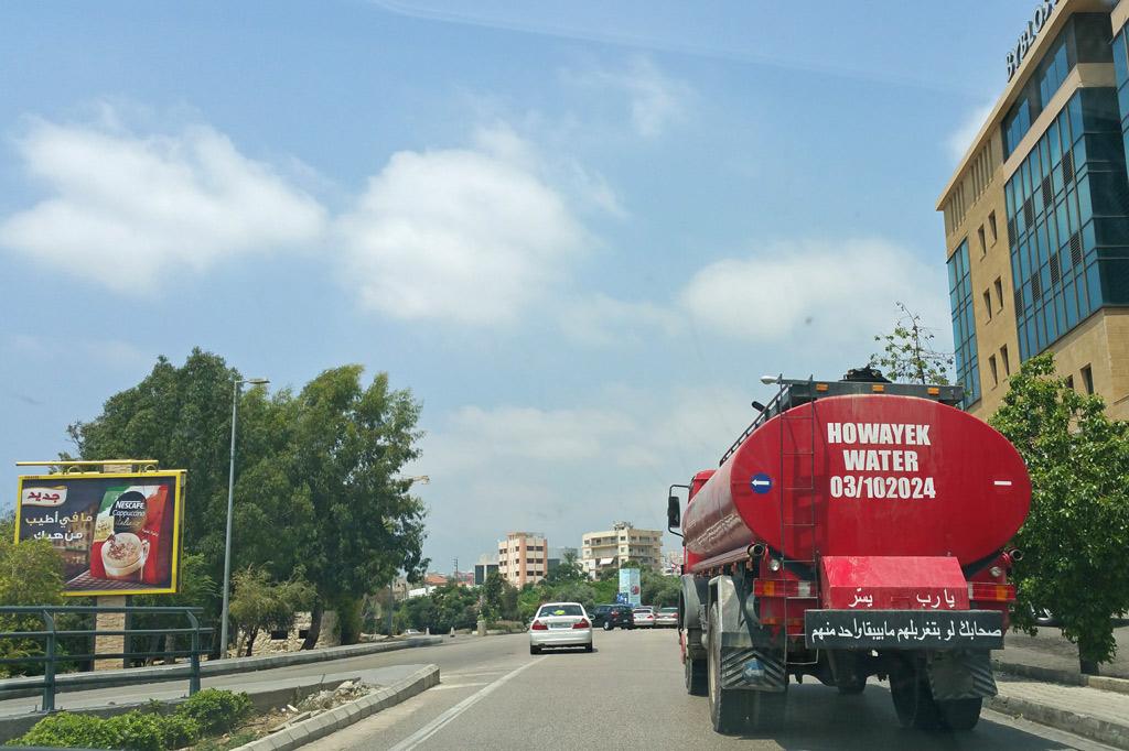 Libanon: Ein Wassertanker vor der Glasfassade eines Hochhauses in Beirut