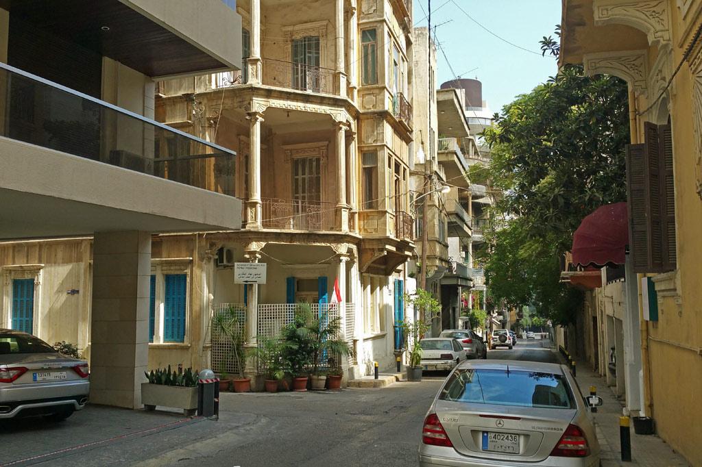 Libanon: Gasse in Beirut mit pastellfarbenen klassizistischen Altbauten, flankiert von nüchterner moderner Architektur