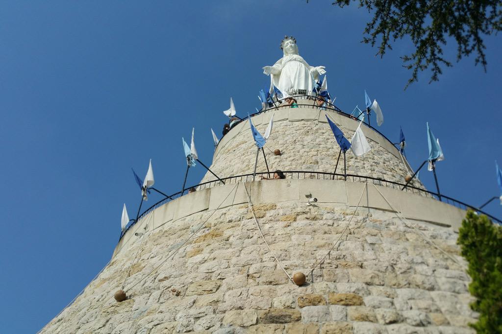Von einem hohen gemauerten Sockel blickt eine weiße Marienstatue – auch Notre Dame des Libanon genannt – herab.