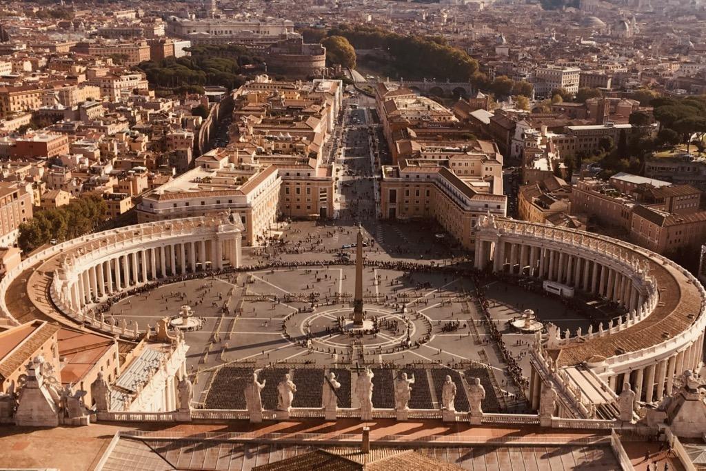 Blick von der Kuppel der Peterskirche über Rom. Die Arkaden Berninis schließen den Petersplatz mit ihren geschwungenen Armen ein. Dieser Ausblick ist ein echter Rom Tipp. Denn diese Aussicht ist wirklich fantastisch.