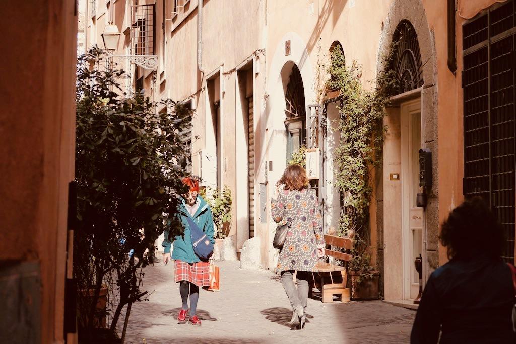 Das Bild zeigt eine schmale Gasse im Ghetto von Rom. Die Sonne scheint. Zwei Frauen gehen durch die schmale Gasse. Flanieren, sich treiben lassen das ist der ultimative Rom Tipp.