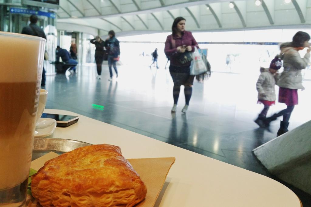 Ein Latte-Macchiato-Glas und eine Apfeltasche in Großformat, im Hintergrund das Untergeschoss des neuen Fernbahnhofs der Stadt. Zusatz zu den Lüttich-Tipps: Gerade sonntags gibt es bei schlechtem Wetter nicht viele Plätze, an denen man gemütlich sitzen kann. Das gilt auch für Lüttichs Altstadt. Deshalb erfreuen sich die Cafés im Bahnhof – vor oder nach einem Stadtrundgang – großer Beliebtheit.