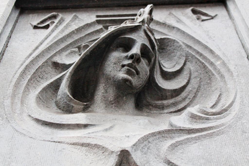 Relief eines Kopfes an einer Hausfassade im Jugendstil. Ein Stadtrundgang zu den Jugendstil-Gebäuden gehört zu den wichtigsten Lüttich-Tipps und erschließt neben der Altstadt auch andere Viertel der Maasmetropole.