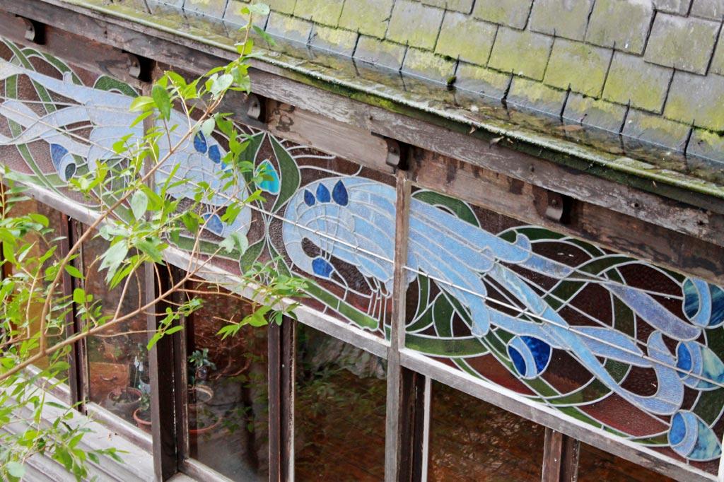 Blick auf ein Fenster mit einer Verzierung aus blauen Pfauen in Glaseinlegearbeit. Jugendstil in Lüttich ist oft unspektakulär, deshalb ist einer der wichtigsten Tipps: Augen auf beim Stadtrundgang, gerade auch außerhalb der Altstadt!