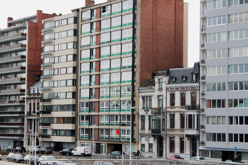 5 Tipps für deinen Stadtrundgang durch Lüttich (Teil 2): Altbauten im Jugendstil und im klassizistischen Stil stehen eingequetscht zwischen modernen Hochhäusern – gesehen am Maas-Ufer am Südrand der Altstadt.