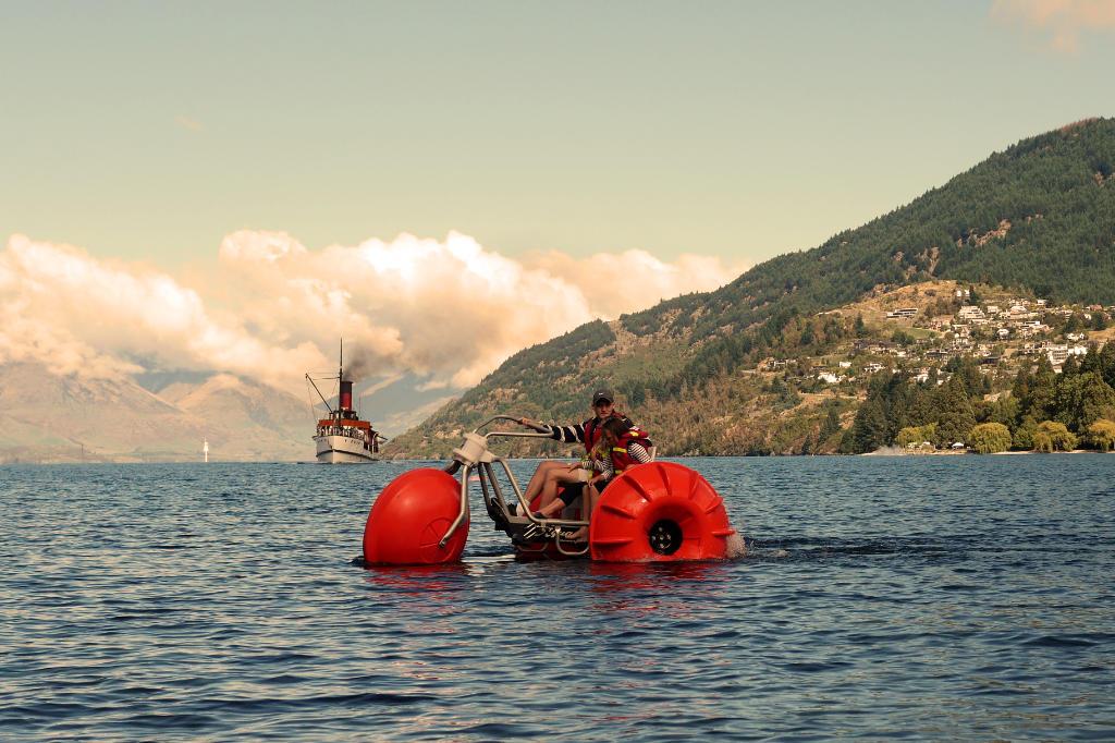 Ein oranges Dreirad mit luftgefüllten Rädern fährt über den Lake Wakatipu bei Queenstown.