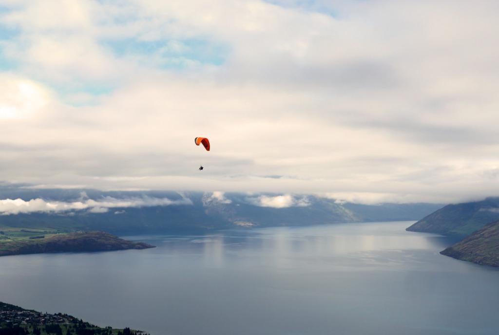 Ein Paraglider fliegt über die spiegelglatte Oberfläche des Lake Wakatipu.