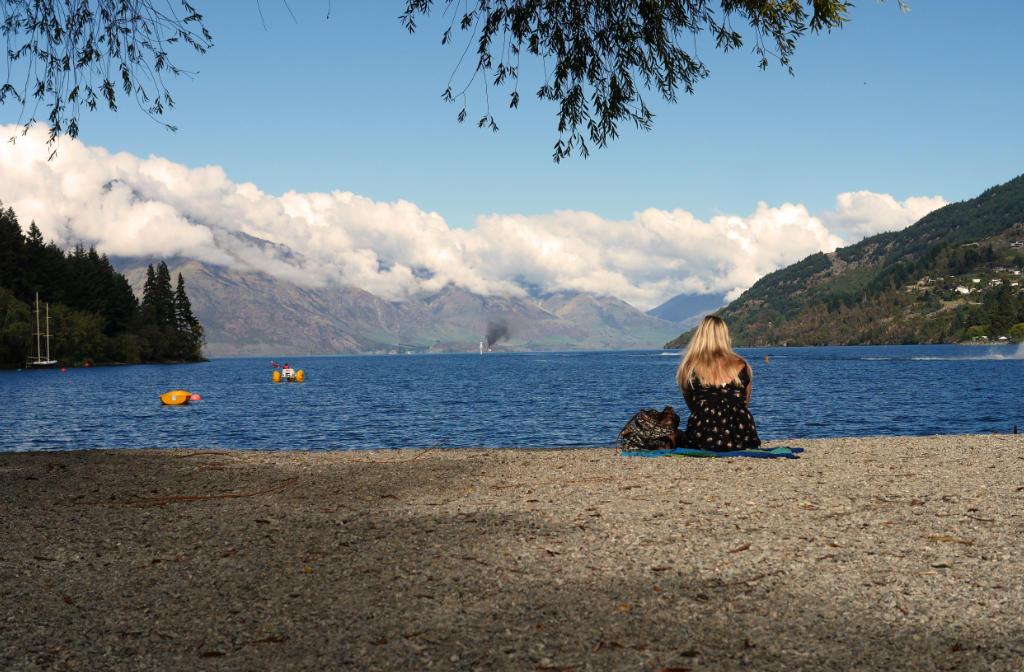 Der Strand des Lake Wakatipu in Queenstown. Eine blonde Frau sitzt alleine am Strand. Im Hintergrund hohe Berge und blauer Himmel.