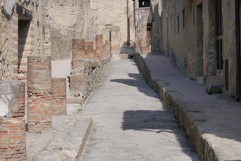 Blick durch eine schmale Straße in Herculaneum. Die hohen Bürgersteige sind von Säulen aus Backstein flankiert.