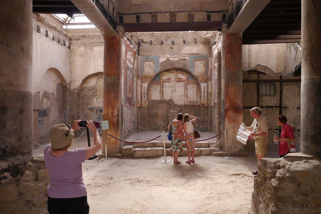 Blcik in ein Atrium. Menschen fotografieren und studieren den Plan von Herculaneum.