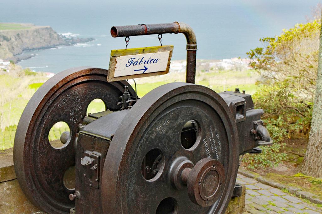 Zum Tee auf die Azoren-Inseln: Ein Schild weist den Weg zur Fabrik, in der der Ertrag der Teeplantagen noch so verarbeitet wird wie vor 100 Jahren. So wird gleich ein lebendes Industriedenkmal daraus – und für uns ein willkommenes Dach über dem Kopf gegen das heute etwas regnerische Wetter.
