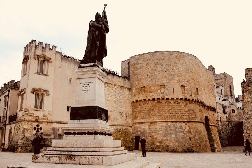 Das Bild zeigt eine Skulptur auf einem hohen Sockel. Die dargestellte Frau soll eine Personifikation Italiens sein, deswegen hält sie eine Fahne in der Hand. Im Hintergrund sind hohe Mauern aus gelbem Kalkstein zu sehen. Otranto ist ein sehr schöner Ort und deswegen ein Apulien Tipp.